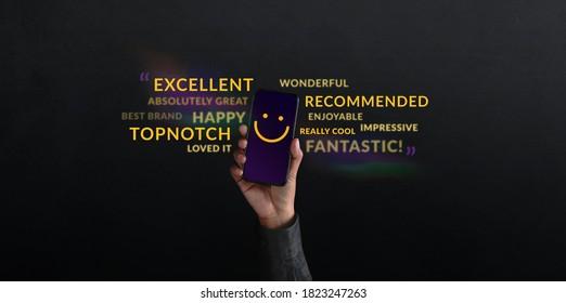 Konzept des Kunden Person hob ein Mobiltelefon mit lächelndem Gesicht Emoticon. Umgeben von Worten des positiven Feedbacks. Befragungen zur Kundenzufriedenheit