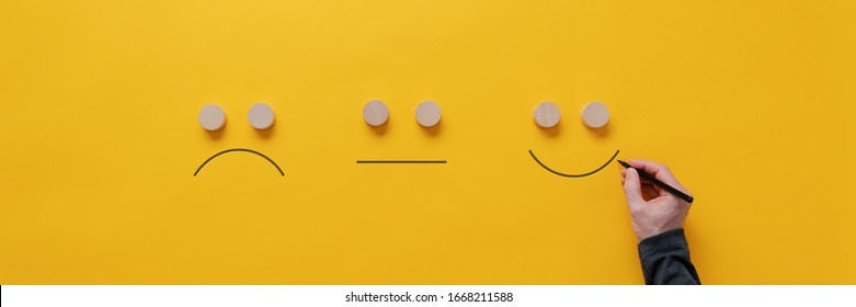 Customer feedback and satisfaction conceptual image - male hand drawing happy, sad and neutral faces over yellow background.