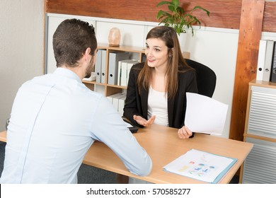Customer and female financial agent in a discussion at desk.