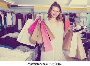 Customer female is holding purchases in apparel store.