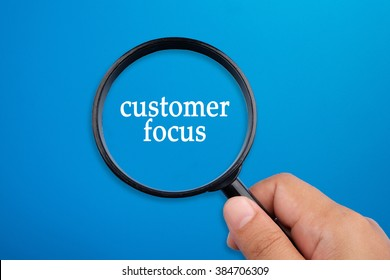 Customer focus, business concepts. Hand holding magnifying glass focusing on the words.
