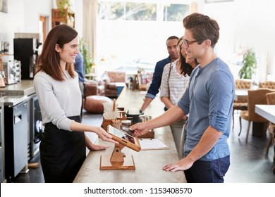 Customer at the front of the queue paying in a coffee shop