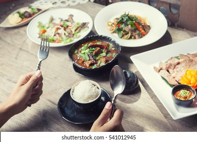 Customer Hand holding spoon and fork on wooden table and eating thai food hot and spicy with steamed rice and cross process filter