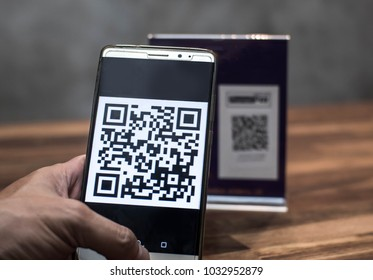 Customer hand using smartphone to make payment by QR code scanning, in cashless era, illustrative editorial