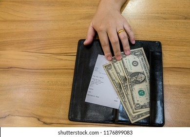 Customer handed the cash on bill paper. US dollar banknote tips in leather black bill reciept. USA Inflation concept.  image for background, wallpaper and copy space. bill checking and tips concept