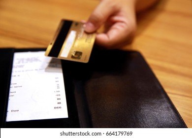 Customer handed the credit card on bill paper, in  leather black bill reciept. image for background, wallpaper and copy space. bill checking and tips concept.