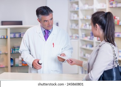 Customer handing a prescription to a pharmacist in the pharmacy