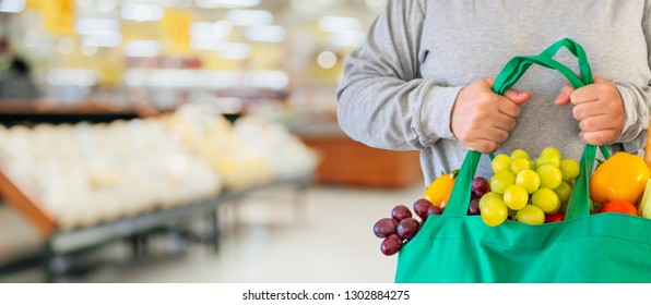 Customer hold reusable green shopping bag with fruit and vegetable over Supermarket aisle blur defocused product shelves interior bokeh light background