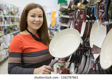 Customer holding white non-stick frying pan in hands while making choice in shop department