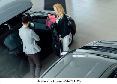 Customer looking at cars at dealership and talking to salesperson