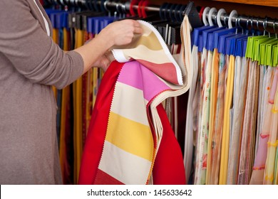 Customer looking at fabric samples hanging on display in an interior decorating shop