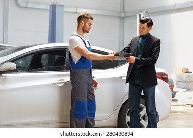 Customer Looking at the Service Report in a Repair Shop