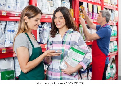 Customer Making Payment To Saleswoman In Pet Shop