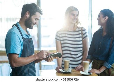 Customer making payment through payment terminal in café
