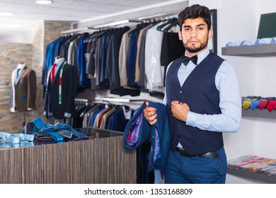 Customer man is demonstrating image in waistcoat with butterfly in shop.