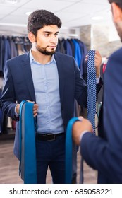 Customer man is picking up tie for jacket in front of the mirror in men's shop.