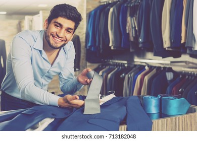 Customer man is showing jacket and tie that he chose in shop.