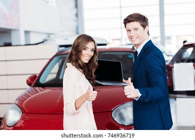 Customer and manager showing thumbs up to the camera in car showroom