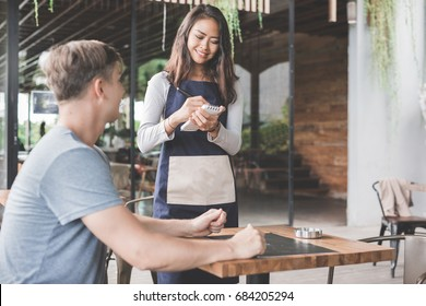 customer ordering food toward waitress at the restaurant