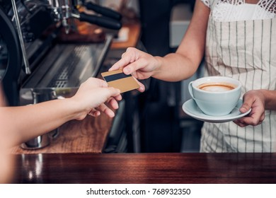 customer pay coffee drink with credit card to barista,Close up hand paid for to go coffee cup at counter bar in cafe,Food and drink business,billing payment