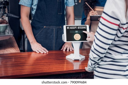 customer pay drink with bitcoins on tablet screen at cafe counter bar,seller coffee shop accept payment by crypto currency.digital money concept