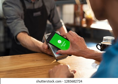 Customer paying bill through smartphone using NFC technology. Closeup of hand making payment through contactless machine. Woman hand holding mobile phone paying the bill with contact less technology.