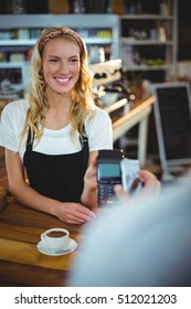 Customer paying bill through smartphone using NFC technology in café
