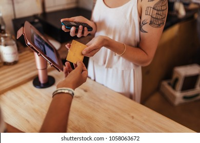 Customer paying the bill using a credit card at a cafe. Woman entrepreneur holding a wireless point of sale machine to effect card transaction.