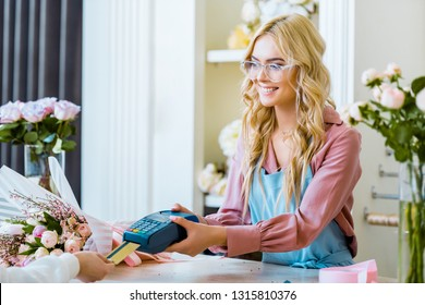 customer paying with credit card it flower shop while beautiful female florist holding terminal