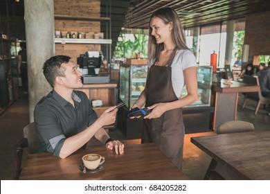 customer paying his bills using credit card, assisted by waitress