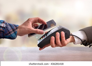 Customer paying a merchant with mobile phone with NFC technology. Top view. Horizontal composition.