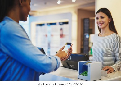 Customer paying for order with phone and pin pad in front of cheerful cashier sales woman at store