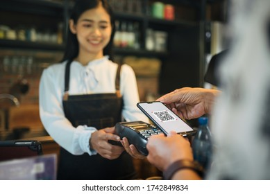 Customer paying with qr code on smartphone screen NFC payment technology at coffee shop.