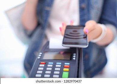 Customer is paying with smartphone in shop