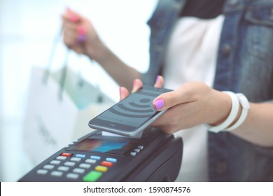 Customer is paying with smartphone in shop using NFC technology. NFC technology. Customer is paying
