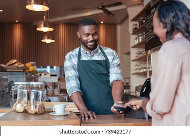 Customer paying a smiling barista for a purchase in a cafe using a smartphone and nfs technology