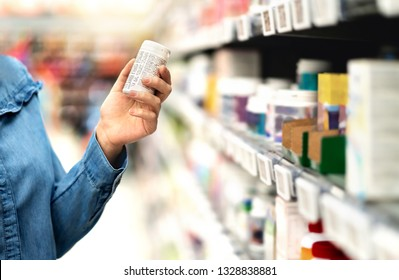 Customer in pharmacy holding medicine bottle. Woman reading the label text about medical information or side effects in drug store. Patient shopping pills for migraine or flu. Vitamin or zinc tablets.