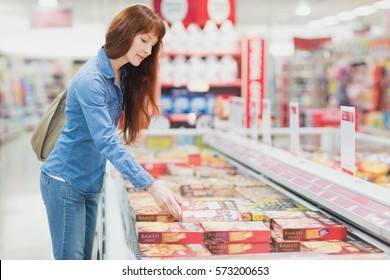 Customer picking a product in the frozen aisle of a supermarket