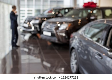 Customer ponders buying a new car. Modern and prestigious vehicles. Themed blur background with bokeh effect.