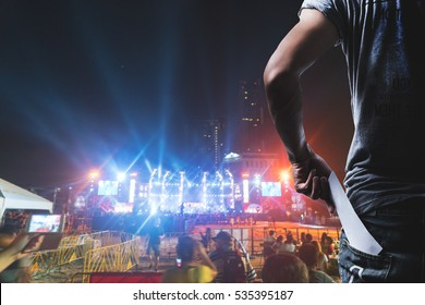 Customer presenting tickets or admission passes watch a rock music concert