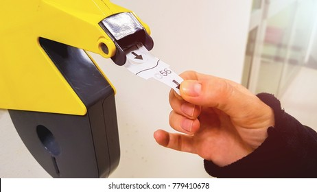 Customer pulls with hand a numbered ticket out of yellow number dispenser machine, to wait in service line and to be served when his number is displayed