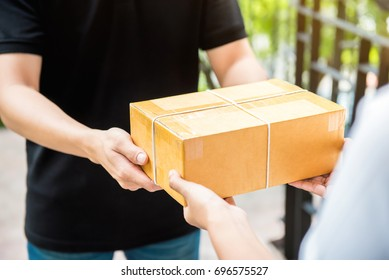 Customer receiving parcel from delivery man - courier and delivery service concept