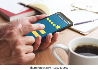 Customer review Concept. Sending five stars rating.Closeup of male hands touching smartphone screen at table.