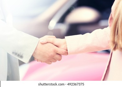 Customer and salesman shaking hands.