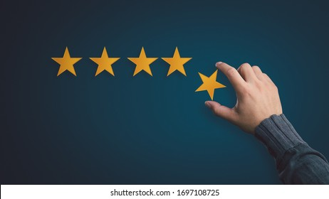 Customer satisfaction concept. hand put the stars to complete five stars. with copy space.giving a five star rating. Service rating, satisfaction concept.