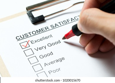 Customer satisfaction survey form on clipboard with red pen
