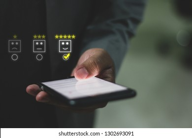Customer service evaluation concept,Businesman pressing face emoticon5 star on the smart phone