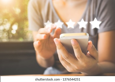 Customer service experience and business satisfaction survey. Woman hand using smart phone with icon five star symbol to increase rating of company concept