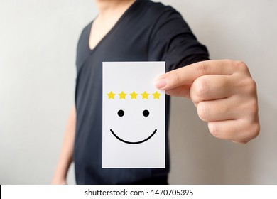 Customer service experience and business satisfaction survey. Man holding card with smiley face with five star