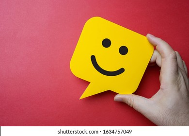 Customer service experience and business satisfaction survey. Man holding yellow speech bubble with smiley face on red background.